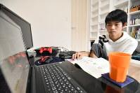 自宅のPCで学校の授業を受ける相原選手(レバ)。机上に置かれたゲーム機を使って競技の練習やオンライン上での大会出場もしている=東京都板橋区2018年6月28日、宮間俊樹撮影