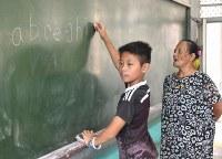 タイヤル語は固有の文字を持たないが、アルファベットを使って表記される。ヤブン・トリ先生(右)の指導でアルファベットを学ぶ澳花小学校の児童=台湾北東部・宜蘭県澳花村で2018年5月23日午前9時26分、福岡静哉撮影