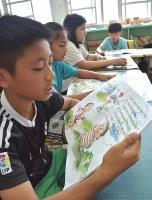 絵付きのタイヤル語教科書を音読をする澳花小学校の児童たち。タイヤル語はアルファベットを使って表記されている=台湾北東部・宜蘭県澳花村の澳花小学校で2018年5月23日午前9時47分、福岡静哉撮影