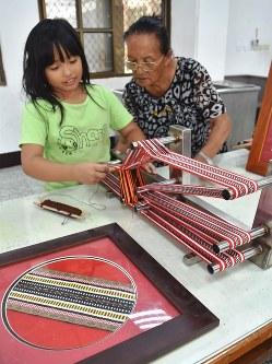 澳花小学校では、タイヤル族の伝統衣装などに使う布の織り方を学ぶ授業もある。児童がヤブン・トリ先生(右)に織り方を教わっている=台湾北東部・宜蘭県澳花村で2018年5月23日午後1時49分、福岡静哉撮影