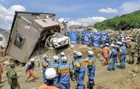 【直後】土砂崩れで住宅が流された現場で救出、捜索活動にあたる警察官ら=広島県熊野町で2018年7月9日、手塚耕一郎撮影