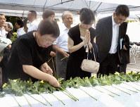広島市原爆死没公務員追悼式で、慰霊碑の前に花を供えて犠牲者の冥福を祈る遺族たち=広島市中区の同市役所で、佐藤英里奈撮影