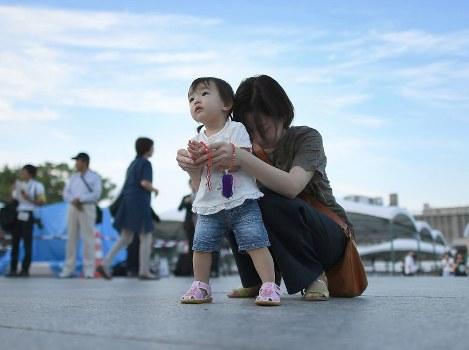 1歳になる長女と一緒に原爆慰霊碑に向かって手を合わせる女性。祖母が被爆し、女性自身も幼い時からに毎年訪れているという。「これからも一緒に、続けたい」=広島市中区の平和記念公園で2018年8月6日午前5時37分、久保玲撮影