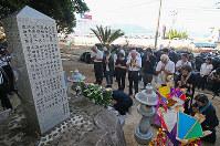 西日本豪雨で一時は土砂に埋まった原爆慰霊碑に向かい、手を合わせる人たち=広島県坂町小屋浦で2018年8月6日午前8時15分、小川昌宏撮影