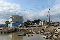 発生から10日が過ぎた鬼怒川の決壊現場。堤防の復旧工事が進む一方、残った水が川のようになっていた。左は周囲の建物が流される中、残った白い家=茨城県常総市で2015年9月20日午後3時31分、徳野仁子撮影