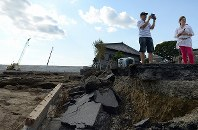 鬼怒川が決壊し、道路が寸断された現場を写真におさめる人たち=茨城県常総市で2015年9月20日午後2時45分、徳野仁子撮影
