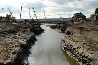 発生から10日が過ぎた鬼怒川の決壊現場。堤防の復旧工事が進む一方、建物やアスファルトが流されて土がむき出しとなり、残った水が川のようになっていた=茨城県常総市で2015年9月20日午後3時39分、徳野仁子撮影