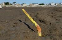 発生から10日が経って水が引いた決壊現場の近くでは、地面から出たパイプが水の流れた方向に折れ曲がっていた=茨城県常総市で2015年9月20日午後3時、徳野仁子撮影