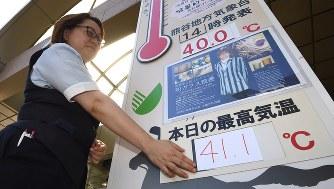 デパート前の気温掲示板の数字を張り替える女性。41度を超える想定をしておらず、手書きで作ったという=埼玉県熊谷市で2018年7月23日、丸山博撮影