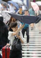 A woman's umbrella is blown inside out due to strong winds triggered by Typhoon Shanshan in Tokyo's Shinjuku Ward, on Aug. 8, 2018. (Mainichi)