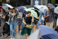 People walk in strong winds due to Typhoon Shanshan in Tokyo's Shinjuku Ward, on Aug. 8, 2018. (Mainichi)