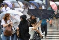 台風の影響で強風が吹くなか歩く人たち=東京都新宿区で2018年8月8日午前9時14分、宮武祐希撮影