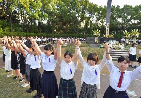 輪になって手をつないで「人間の鎖」をつくる高校生ら=長崎市の爆心地公園で2018年8月9日午前6時51分、森園道子撮影