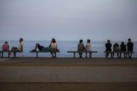 海辺で涼む人々。アフリカから吹き込む高温の空気の影響で記録的な暑さが続いている=スペイン東部バルセロナで2日、AP