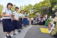 High school students prepare to lay flowers next to a photo of the late Sumiteru Taniguchi, an atomic bomb survivor from Nagasaki who dedicated his life to the abolition of nuclear weapons, in front of the Hypocenter Cenotaph at Bakushinchi (Hypocenter) Park on Aug. 9, 2018. (Mainichi)