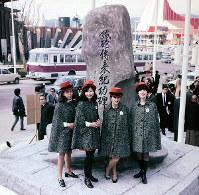 複製した種子島の「鉄砲伝来記功碑」の前に立つポルトガル館のホステス=1970年3月