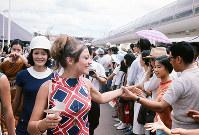 閉会式後、会場内をパレードする各パビリオンのホステスやホストたちは、入場客と握手をして別れを惜しんだ=1970年9月13日