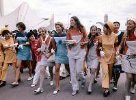 閉会式後、腕を組んで会場内をパレードする各パビリオンのホステスやホストたち=1970年9月13日