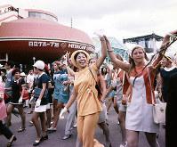 閉会式後、入場客に手を振りながら会場内をパレードする各パビリオンのホステスやホストたち=1970年9月13日