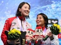 女子400メートル個人メドレー決勝で優勝して笑顔を見せる大橋(左)と3位の清水=東京辰巳国際水泳場で2018年8月9日、佐々木順一撮影