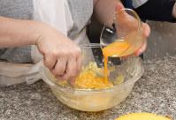 バターはポリ袋に入れてもみ、ボウルに砂糖を入れ、溶き卵を加えて混ぜる=根岸基弘撮影