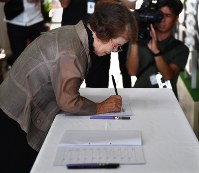 A woman signs her name on a condolence book on Aug. 10, 2018, at the Okinawa Prefectural Government headquarters, following the death of Okinawa Gov. Takeshi Onaga two days earlier. (Mainichi)