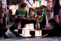 初めて3人で灯籠を流す(中央左から)小澤秀明さん、妻裕美さん、母紀美さん=群馬県上野村で2018年8月11日午後6時54分、喜屋武真之介撮影