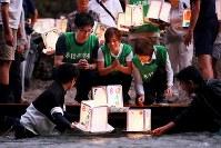日航ジャンボ機墜落事故発生から33年を前に、初めて3人で灯籠を流す(中央左から)小澤秀明さん、妻裕美さん、母紀美さん=群馬県上野村で2018年8月11日午後6時54分、喜屋武真之介撮影