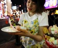 歓楽街ススキノのネオンに映える札幌生まれのシメパフェ=札幌市中央区で2018年8月2日、貝塚太一撮影