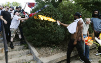 In this Aug. 12, 2017 photo, a counterdemonstrator uses a lighted spray can against a white nationalist demonstrator at the entrance to Lee Park in Charlottesville, Virginia. (AP Photo/Steve Helber)