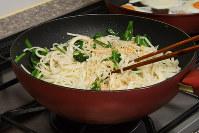 フライパンに油を入れ、うどんを入れて、ツナ、ニラの順に加えて混ぜる。ナンプラー、コショウ、粉ザンショウで調味する=根岸基弘撮影