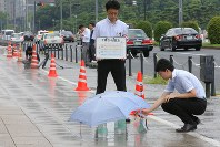 Officials of the Tokyo Metropolitan Government and other authorities measure the surface temperature of a sidewalk sprayed with water in the capital's Chiyoda Ward on Aug. 13, 2018. (Mainichi)