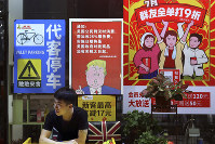 In this Aug. 13, 2018, photo, a man stands near a poster depicting a mural of U.S. President Donald Trump stating that all American costumers will be charged 25 percent more than others starting from the day president Trump started the trade war against China, on display outside a restaurant in Guangzhou in south China's Guangdong province. (Color China Photo via AP)