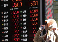 A woman checks the currency exchange rates at a currency exchange shop in Istanbul, on Aug. 13, 2018. (AP Photo/Lefteris Pitarakis)