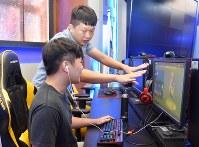 学生(手前)にeスポーツ技術を指導する呂家宏さん=台湾中部・台中市の僑光科技大で2018年8月1日、福岡静哉撮影