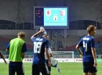 【日本―ネパール】 初戦でネパールに1―0で勝ったことを示す電光掲示板。手前は観客へのあいさつに回る日本代表の選手たち=インドネシア西ジャワ州チカランのウィバワ・ムクティ競技場で2018年8月14日、宮間俊樹撮影
