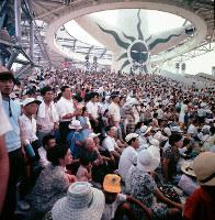 お祭り広場のイベントを見る大勢の入場客たち=1970年夏