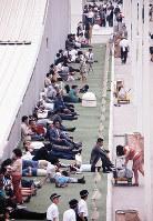 パビリオンの影で休む入場客=せんい館脇で1970年