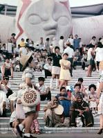 階段に座って休憩する入場者たち=1970年