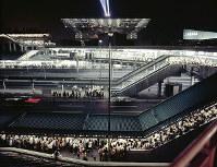 会場を引き上げる人たちで混雑する中央口タクシー乗り場(手前)=1970年