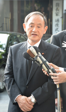 Chief Cabinet Secretary Yoshihide Suga responds to reporters' questions after attending Okinawa Gov. Takeshi Onaga's wake in the Okinawa Prefecture capital of Naha on Aug. 10, 2018. (Mainichi)