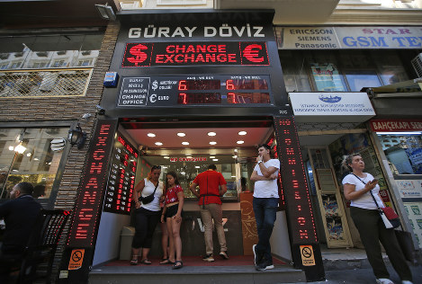 People wait at a currency exchange shop in Istanbul, on Aug. 14, 2018. (AP Photo/Lefteris Pitarakis)