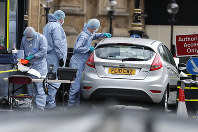 Forensics officers work near the car that crashed into security barriers outside the Houses of Parliament in London, on Aug. 14, 2018. (AP Photo/Frank Augstein)