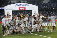 In this Aug. 11, 2018 photo, Real Madrid players pose with the trophy after winning the Santiago Bernabeu trophy soccer match between Real Madrid and AC Milan at the Santiago Bernabeu stadium, in Madrid. (AP Photo/Andrea Comas)