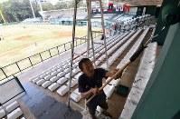 白色だった野球会場・内野スタンドの壁を緑色に塗り直す作業員=ジャカルタで2018年8月12日、宮間俊樹撮影