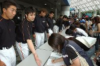 近鉄とオリックスの合併反対の署名活動をする高橋由伸(左から2人目)ら巨人の選手=東京ドームで2004年7月29日、山本晋撮影