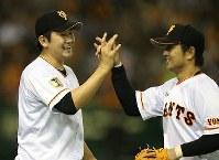 【巨人3-2DeNA】七回表DeNA1死満塁、石川雄洋の飛球を左翼手・高橋由伸(右)が捕って本塁に返球し三塁走者もタッチアウト。先発投手の菅野智之(左)と笑顔でハイタッチ=東京ドームで2015年3月27日、山本晋撮影