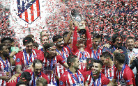 Atletico's Antoine Griezmann lifts up the trophy to celebrate with teammates after the UEFA Super Cup final soccer match between Real Madrid and Atletico Madrid at the Lillekula Stadium in Tallinn, Estonia, on Aug. 15, 2018. (AP Photo/Pavel Golovkin)