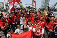 開幕を翌日に控えたアジア大会のモニュメント前でインドネシアの独立記念日を祝福する人たち=ジャカルタで2018年8月17日、宮間俊樹撮影