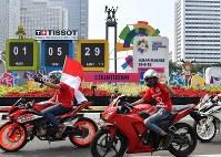 インドネシアの独立記念日を祝福しながらアジア大会開幕までのカウントダウンボード前を通過する人たち。後方奥は前回ジャカルタで開催されたアジア大会を記念して建立されたモニュメント=ジャカルタで2018年8月17日、宮間俊樹撮影